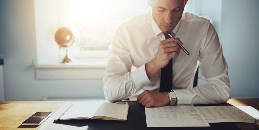 Executivo com dúvidas e analisando relatórios sobre a mesa do escritório