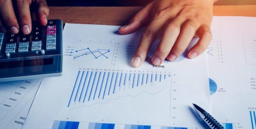 Executivo calculando a finança e a contabilidade com relatórios e calculadora sobre a mesa do escritório