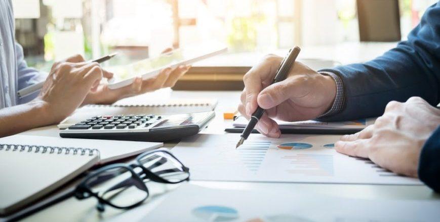 Profissionais do financeiro calculando ou verificando relatórios de finanças.