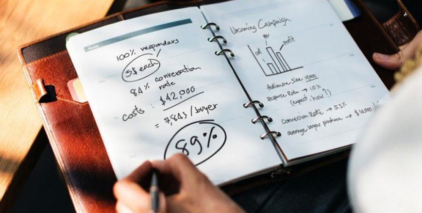 Executiva calculando custos em seu caderno de anotações
