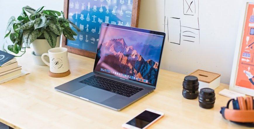 Mesa de trabalho com notebook e materiais de escritório.