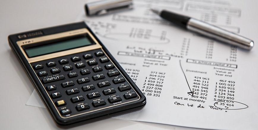 Mesa de escritório com relatórios e calculadora.
