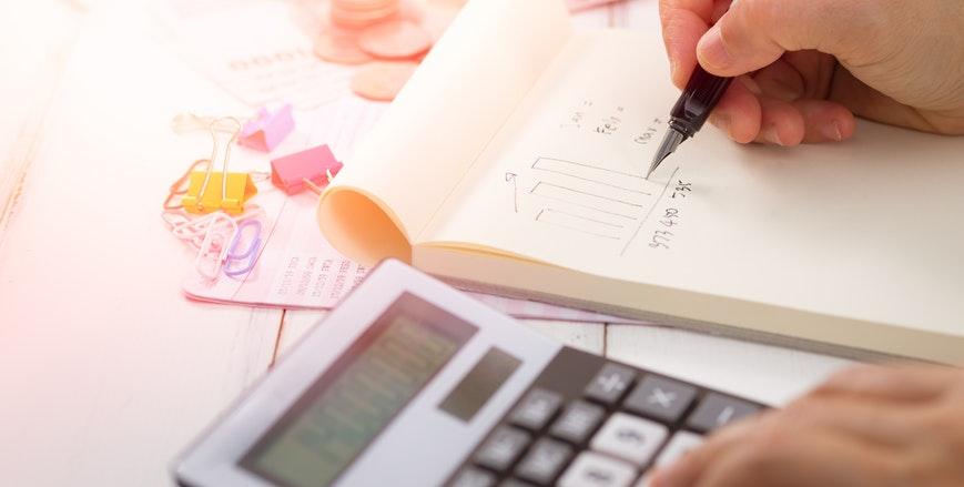 Profissional iniciando o Fluxo de Caixa Indireto em um bloco de nota sob uma mesa e com calculadora ao lado.